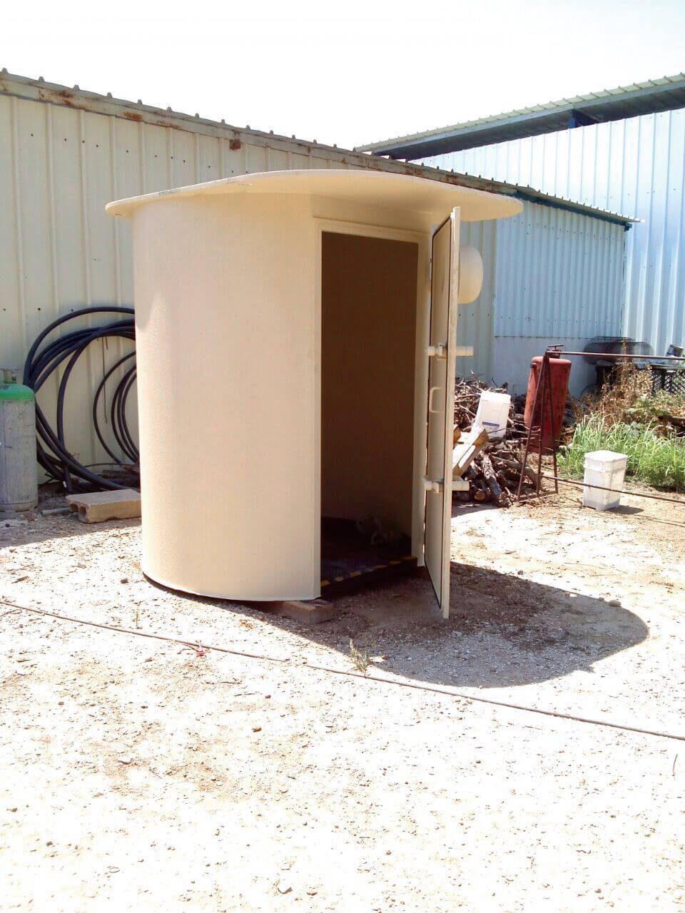 מיגונית עם דלת פתוחה בחצר מפעל